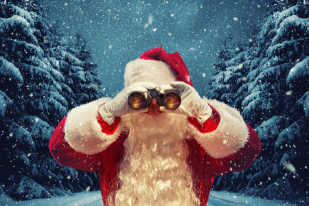 Santa Claus looking through binoculars.  Christmas concept. Santa on the background of a fabulous night winter forest.