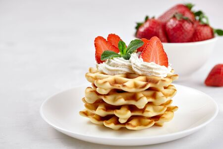 Beautiful breakfast. Homemade Belgian Viennese waffles decorated with strawberries, tea on a light background.