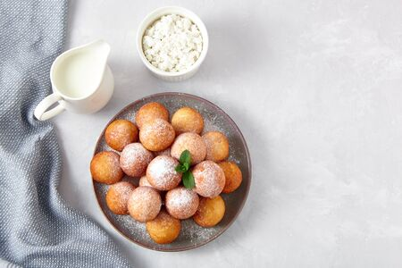 Beautiful breakfast. Cottage cheese donuts  balls  on a light background. Top view.