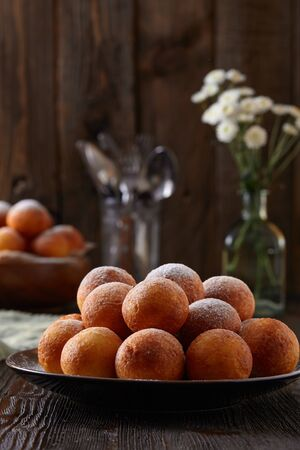 Cottage cheese donuts on a dark wooden rustic background.