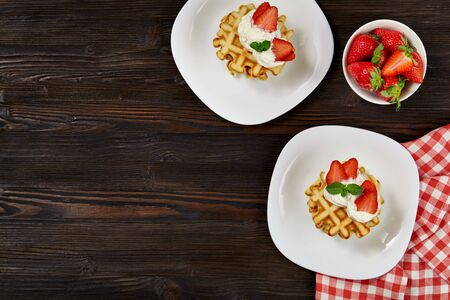 Beautiful breakfast. Belgian Viennese waffles decorated with cream and strawberries, tea and a checkered napkin on a dark wooden rustic background.