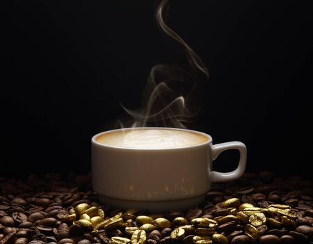 A cup of coffee with smoke on golden coffee beans on a dark background. Space for adding text. 스톡 콘텐츠