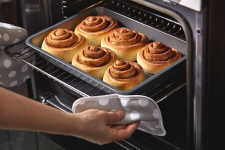 A woman takes out fresh cinnabons from the oven. Ñinnamon rolls are baked in the oven. Homemade baking. 스톡 콘텐츠