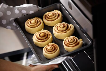 A woman is putting cinnabons in the oven. Ñinnamon rolls are baked in the oven. Homemade baking.