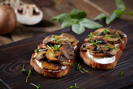 Bruschetta with mushrooms, cream cheese and microgreens on a wooden rustic background.