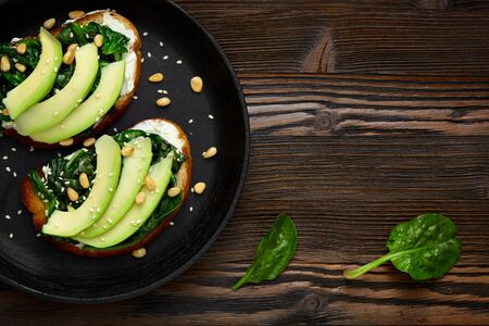 Sandwich with avocado, spinach  in a pan. Dark rustic wooden background and place for an inscription. Top view. Banque d'images