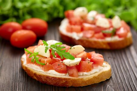 Homemade bruschetta with tomatoes and mozzarella on a rustic wooden board.