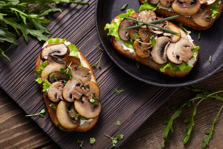Sandwich with mushrooms and cream cheese on a rustic wooden background ñlose-up. 스톡 콘텐츠