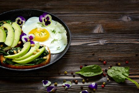 Sandwich with avocado, spinach and fried egg in a pan. Dark rustic wooden background and place for an inscription. Banque d'images
