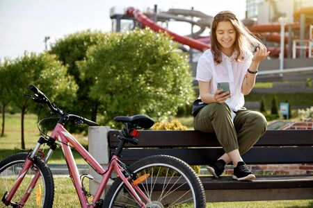 Urban biking teenage girl with phone, bike in city.  Active lifestyle. Banque d'images