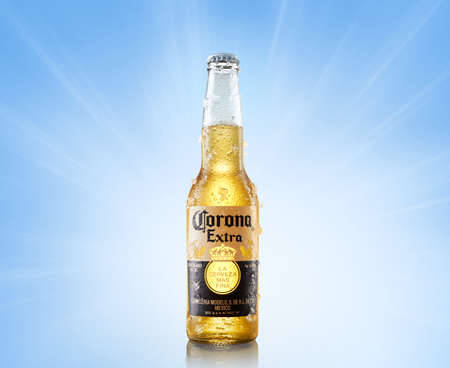 MINSK, BELARUS, june 26, 2020: Chilled bottle of Corona Extra beer bottle of beer on a light blue background in bright rays.