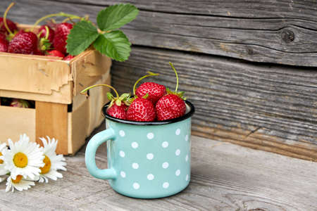 Ripe, fresh strawberries in an enamel mug on a rustic, wooden background. Banque d'images