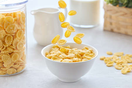 Traditional breakfast with cornflakes and milk. Cornflakes falling into a bowl. Banque d'images