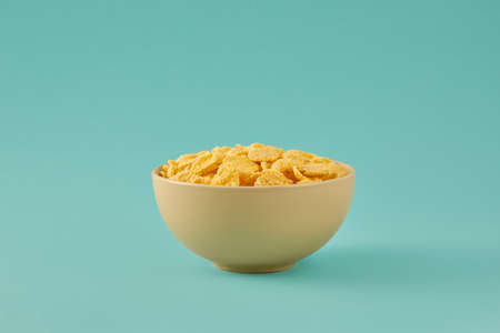 Traditional breakfast with cornflakes. Cornflakes in a light beige bowl on a colored turquoise background. Banque d'images
