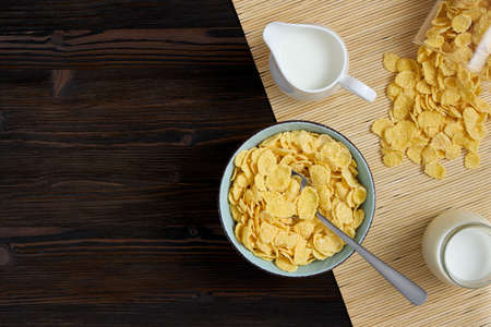 Top view of cornflakes in a plate and milk on a wooden background. Space for text. Banque d'images