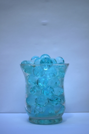 lonelyness: lightblue waterballs in a cup of glass in front view Stock Photo