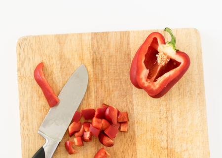 Chopping a Red Bell Pepper on a Wooden Cutting Board Archivio Fotografico