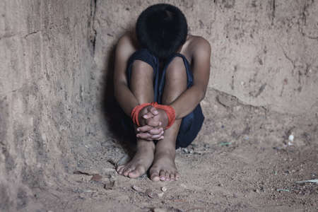 Kidnapped little boy tied with rope.Abused and tortured concept. Human trafficking concept.Stop abusing violence. Standard-Bild
