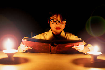 Cute little girl with glasses reading book with lighting candle at night time.