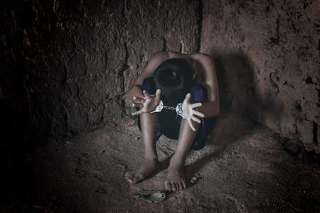 little boy tied with chained. Abused and tortured concept. Human trafficking concept. Stock Photo