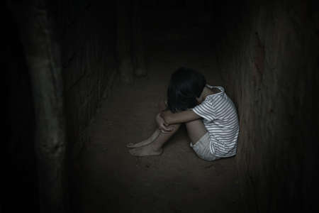 Kidnapped little girl sitting in old dark room. Human trafficking concept. Banque d'images