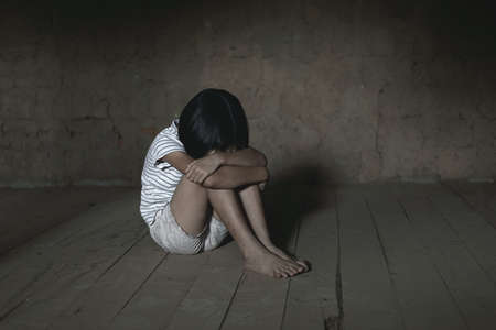 Helpless child sitting on floor against old earth brick wall,children violence and abused concept,human trafficking concept Banque d'images