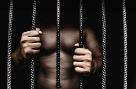 Young man desperate to catch the iron prison,prisoner concept,