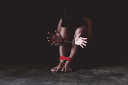 Arrested girl with handcuffs on black background. Hands and legs of a missing kidnapped, abused, hostage, victim woman tied up with rope in pain