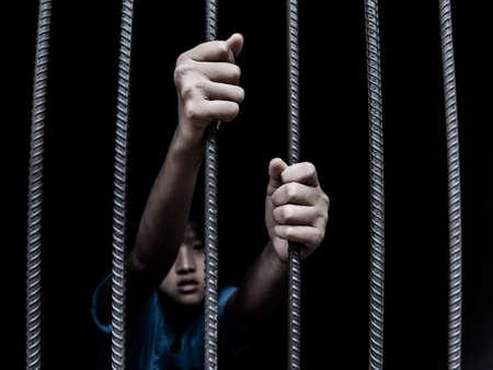 sad child holding a steel cage in old iron bar. children prison and prisoner concept Banque d'images