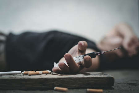 Male of a drug addict and a syringe with narcotic syringe lying on the floor. Anti drug concept.