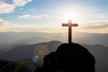 Silhouettes of cross on top mountain with bright sun on the colorful sky background