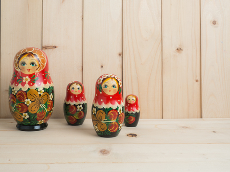 table top: Travel around the world for your colorful life .Enjoy the funny trip journey .Top view for copy space some idea your create destination .object  cute  ,  Set of matrioshka dolls on pine wood  background.