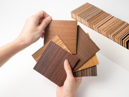 Muestras de madera de la chapa en el fondo blanco. material selecto del diseño interior para la idea. Mano que sostiene la madera de la chapa.