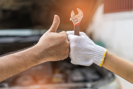 Mechanic hand checking and fixing a broken car in  garage.hand of mechanic with thumbs up and tool Stock Photo