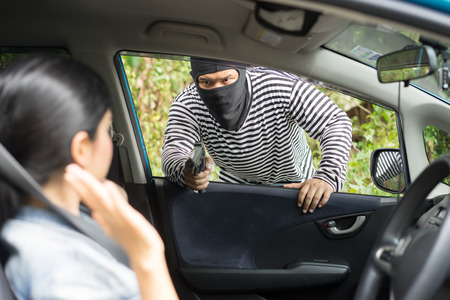 Robber pointing a gun to scare young woman and try to rob her car.andit man with masked robber holding handgun weapon gangster to hijack hostage woman driver car .