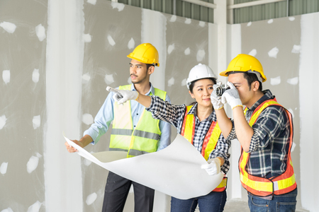 Engineers visit the construction site. Examining blueprint with construction manager.