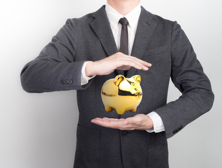 Young man giving hand on black background.Hands open businessman. Piggy bank are here.Saving money concept.