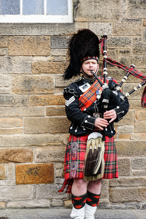 EDINBURGH, SCOTLAND, 24 March 2018 , Scottish bagpiper dressed in traditional red and black tartan dress stand before stone wall. Edinburgh, the most popular tourist city destination in Scotland. Editoriali