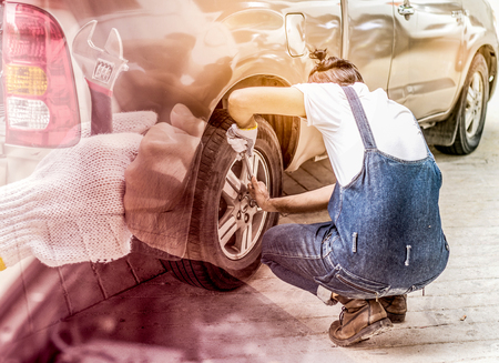 Car mechanic changing tire in the service..Double exposure color effect .