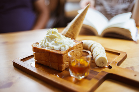 Honey bread with caramel syrup and fresh cream. Ice cream and banana slice with bread on plate.
