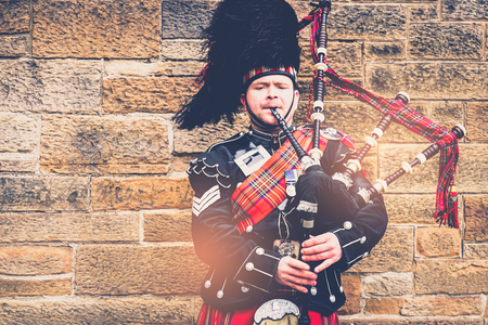 EDINBURGH, SCOTLAND, 24 March 2018 , Scottish bagpiper dressed in traditional red and black tartan dress stand before stone wall. Edinburgh, the most popular tourist city destination in Scotland. Banque d'images