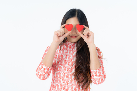 Photo of asian curious woman in red dress rejoicing her birthday or new year. Young woman holding red heart being excited and surprised  holiday present isolated white background 免版税图像