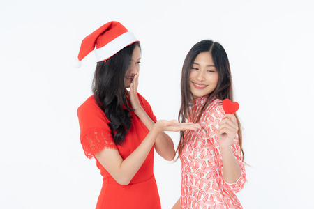 Photo of asian curious woman in red dress rejoicing her birthday or new year. Young two woman holding red heart being excited and surprised  holiday present isolated white background Banco de Imagens