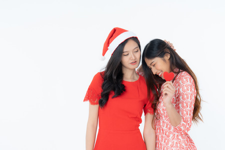 Photo of asian curious woman in red dress rejoicing her birthday or new year. Young two woman holding red heart being excited and surprised  holiday present isolated white background Imagens