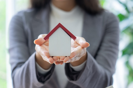 architecture, building, construction, real estate and property concept - close up of hands holding house  model.Home loan property ownership assurance concept Stock Photo