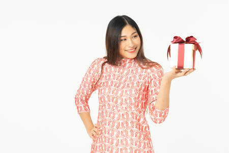 Photo of asian curious woman in red dress rejoicing her birthday or new year gift box. Young woman holding gift  box with red bow being excited and surprised  holiday present isolated white background