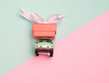 Vintage car carry a  gift box on color background and top wood table for Christmas and The New Year and Valentine's day .Decoration love heart .