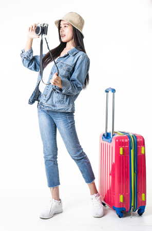 Beautiful young woman smiling and pulling pink color luggage isolated on white background.Asian woman going to summer vacation.Travel trip funny. Banque d'images