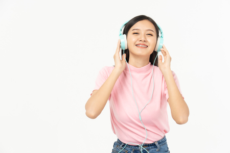 Happy asian teen passenger listening to the music with headphones while holding  mobile phone.businesswoman listening to music with headphones while dancing isolated over white background