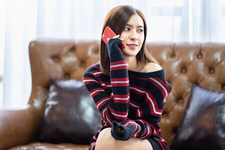 Happy female  holding mobile for shopping online. Asian young beauty woman smile and   sofa . Relaxing time. Reklamní fotografie